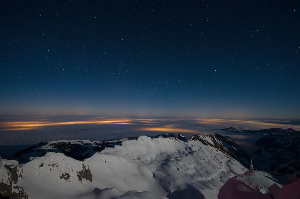 Blick vom Säntis bei Nacht Richtung Nord-Osten. Rechts, der rote Punkt, markiert den Hohen Kasten. Im Hintergrund leuchten unter der Hochnebeldecke die Lichter der Ortschaften.
